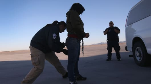 A security contractor frisks a detainee ahead of a deportation flight to Honduras.