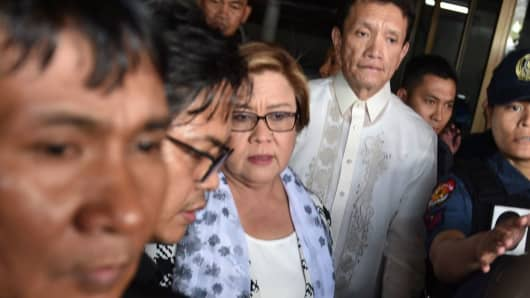 Philippine Senator Leila De Lima (C), a top critic of President Rodrigo Duterte, is escorted by police officers and her lawyer Alex Padilla (R, in white long sleeves) after her arrest at the Senate in Manila on February 24, 2017.