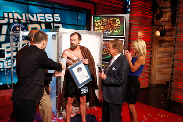 Wim Hoff (C) is congratulated by American TV hosts Regis and Kelly after he stood in a box filled with ice up to his neck, in New York, on the 16th of September 2009. Hoff, beat his own world record for standing in a box of ice bvy staying in the box for 1 hour and 43 minutes, beating his previous record by 1 minute.