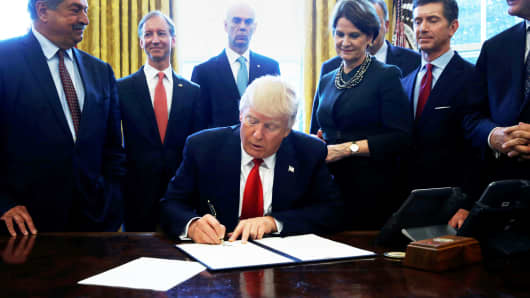 President Donald Trump is surrounded by business leaders as he signs an executive order on regulatory reform at his desk in the Oval Office at the White House, U.S. February 24, 2017.