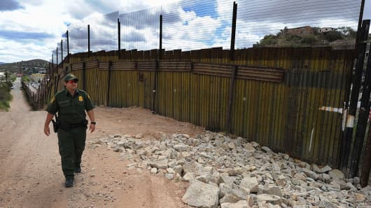 US Border Patrol officer keeps watch over the border fence that divides the US from Mexico