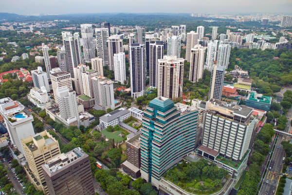 Private residential buildings, foreground, stand in the Orchard Road area of Singapore.
