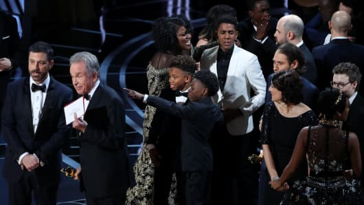 "Presenter Warren Beatty holds up the card confirming that ""Moonlight"" won the Best Picture Oscar as show host Jimmy Kimmel (L) looks on after ""La La Land"" was mistakenly named as the winner."