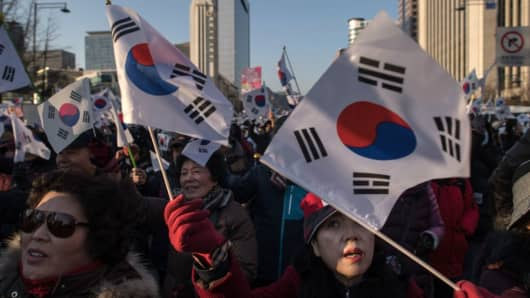 Pro-government activists shout slogans and wave flags as they stage a rally in central Seoul on February 25, 2017. South Korea's Constitutional Court will hold its final impeachment hearing to rule on the fate of President Park Geun-Hye at the end of the month, Yonhap News Agency reported February 22.