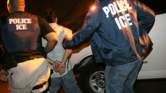 Immigrations and Customs Enforcement (ICE) agents raid homes to arrest specific illegal immigrants.
