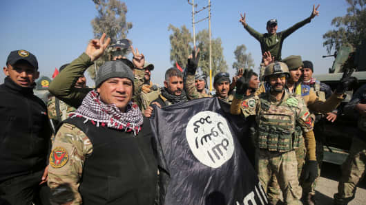 Iraqi forces flash the sign for victory while holding an Islamic State (IS) group flag on February 23, 2017, as they enter Mosul airport on the southern edge of the jihadist stronghold for the first time since the Islamic State group overran the region in 2014.