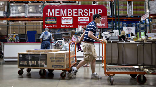 A customer pushes a cart of outdoor items past a membership desk at a Costco Wholesale Corp. store in Naperville, Illinois.