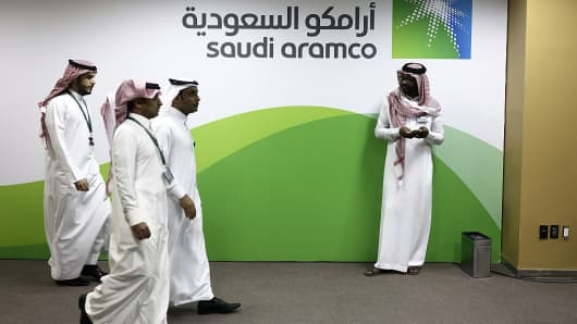 Attendees walk by a sign for the Saudi Arabian Oil Co.