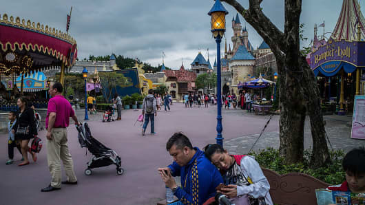 Visitors play smartphones inside Disneyland on April 19, 2016 in Hong Kong, Hong Kong.