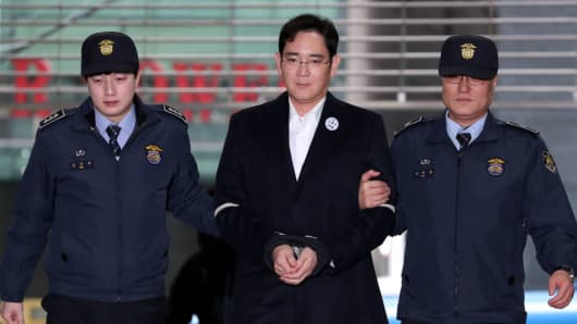 Jay Y. Lee, co-vice chairman of Samsung Electronics, center, is escorted by police officers as he arrives at the special prosecutors' office in Seoul, South Korea, on Sunday, Feb. 19, 2017.