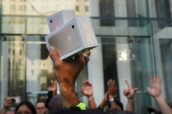 One of the first customers to buy a new iPhone walks out of an Apple store in Manhattan on September 16, 2016 in New York City.