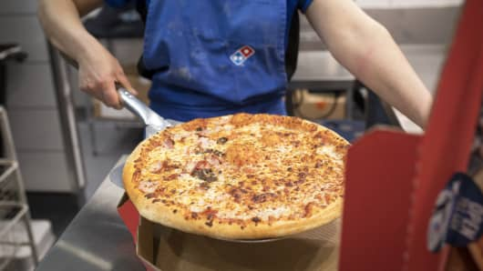 An employee places a cooked pizza into a delivery box inside a Domino's Pizza Group Plc store.