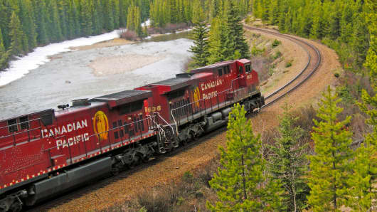 Canadian Pacific double locomotives rounding bend in the Bow river. Alberta.