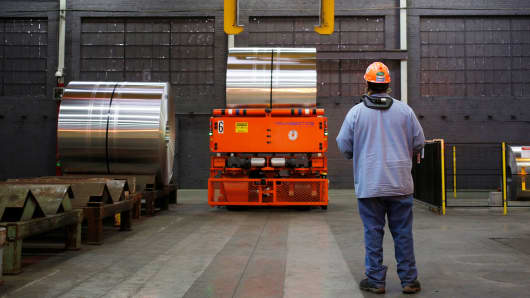 A worker controls a crane to move an aluminum coil at the Arconic manufacturing facility in Alcoa, Tennessee.