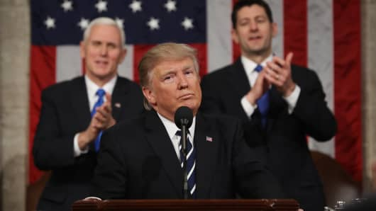 President Donald Trump, center, pauses as U.S. Vice President Mike Pence, left, and U.S. House Speaker Paul Ryan, a Republican from Wisconsin, applaud during a joint session of Congress in Washington, D.C., U.S., on Tuesday, Feb. 28, 2017.