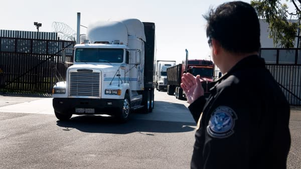 A U.S. Customs and Border Protection official directs trucks at the Mexico border.
