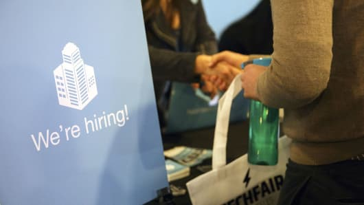 A 'We're Hiring' sign is displayed as a job seeker shakes hands with a representative during the TechFair LA job fair in Los Angeles.