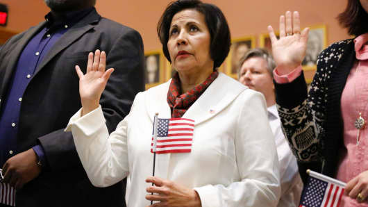 Colombian Born Lucrecia Arbelaez and other candidates take the oath of allegiance to become US citizens during a Naturalization Ceremony for new US citizens at the City Hall of Jersey City, New Jersey on February 22, 2017.
