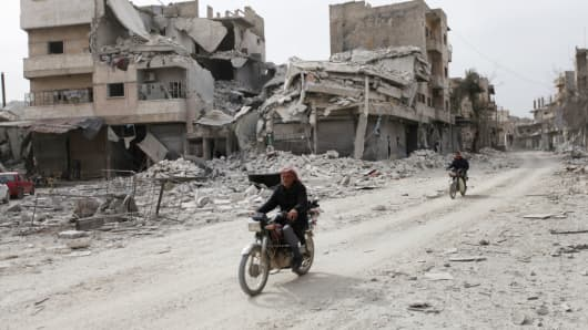 Men ride motorcycles near damaged buildings in the northern Syrian town of al-Bab, Syria, February 28, 2017.