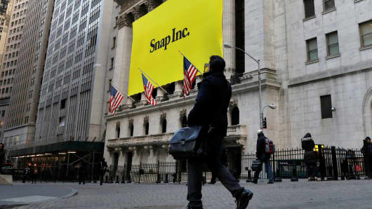A man photographs a banner for Snap Inc. on the facade of the New York Stock Exchange on the morning of the company's IPO in New York City, March 2, 2017.