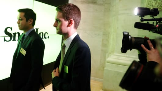 Snap co-founders Evan Spiegel (R) and Bobby Murphy walk until the first call of the New York Stock Exchange on March 2, 2017.