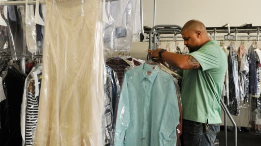 Everette Lange collects cleaned and pressed garments for a customer at Any Garment Cleaners in Aurora, Colorado.
