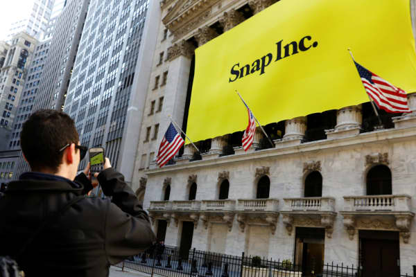 A man takes a photograph of the front of the New York Stock Exchange with a Snap Inc. banner shortly before the company's IPO, March 2, 2017.