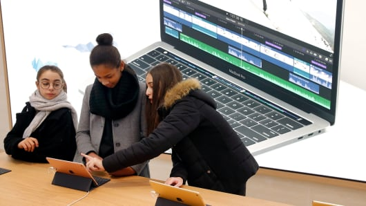 Customers check iPad tablets in an Apple store.