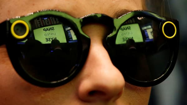 A woman wears Snapchat's Spectacles on the floor of the New York Stock Exchange during the company's initial public offering in New York, March 2, 2017.