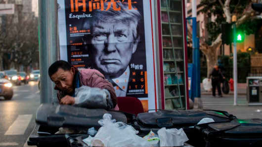 This picture taken on March 2, 2017 shows a man searching rubbish bins in front of an news stand advertising a Chinese newspaper with the front page photo of U.S. President Donald Trump.
