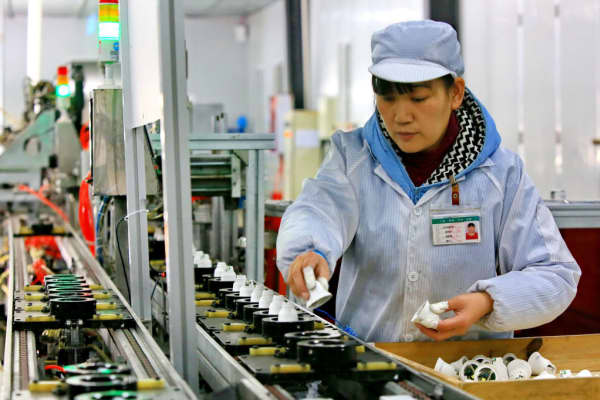 An employee works on an energy-saving bulb production line at a factory in Suining, southwest China's Sichuan province.