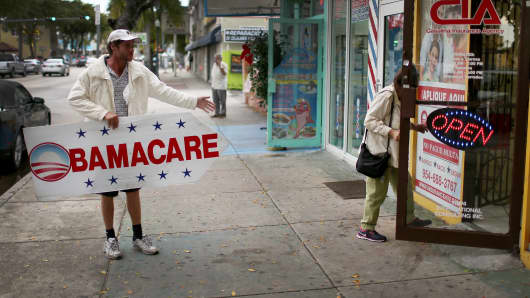 Pedro Rojas holds a sign directing people to an insurance company where they can sign up for the Affordable Care Act, also known as Obamacare, before the February 15th deadline on February 5, 2015