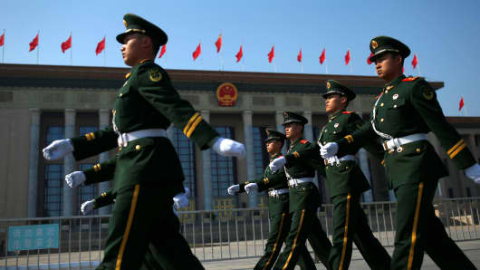 Security personnel march in front of the Great Hall of the People in Beijing, China.