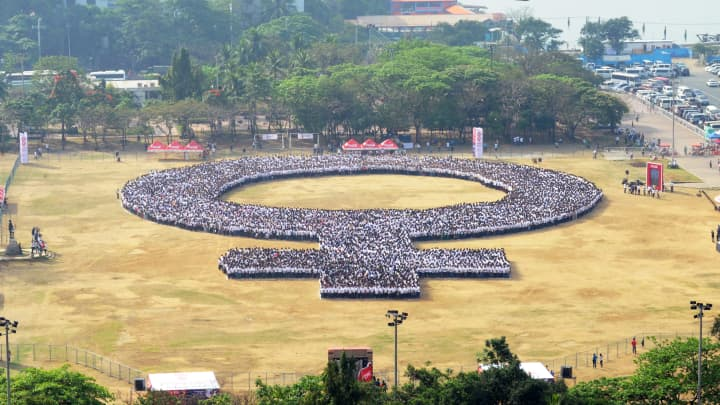 People gather to form a woman symbol to celebrate International Women's Day at Manila's Rizal Park on March 8, 2014.