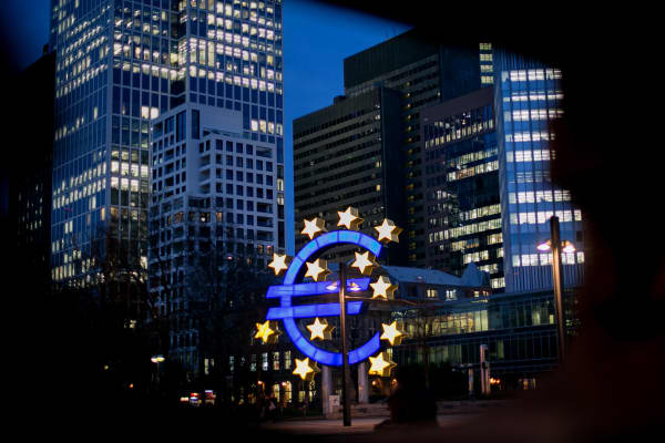 The euro sign sculpture stands illuminated near the former European Central Bank (ECB) headquarters at dusk in Frankfurt, Germany.