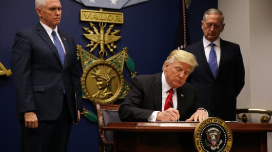 President Donald Trump signs a revised executive order for a U.S. travel ban on Monday, leaving Iraq off the list of targeted countries, at the Pentagon in Washington.
