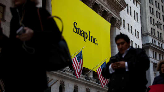 Pedestrians pass in front of Snap Inc. signage displayed on the exterior of the New York Stock Exchange (NYSE) during the company's initial public offering (IPO) in New York, U.S., on Thursday, March 2, 2017.