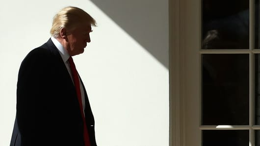 President Donald Trump walks to the Oval Office after arriving back at the White House.