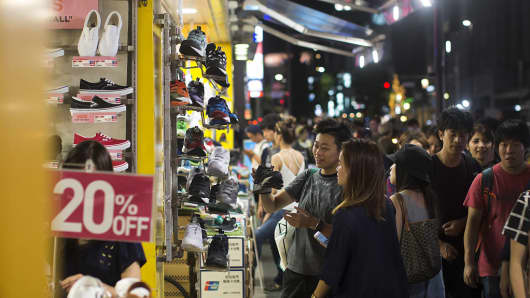 Shoppers walk past a shoe store in the Omotesando area of Tokyo, Japan, on Sep. 3, 2016.