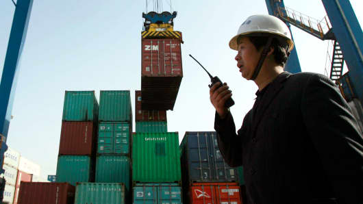 A worker monitors the loading of shipping containers at the new container port in Wuhan, in central China's Hubei province.