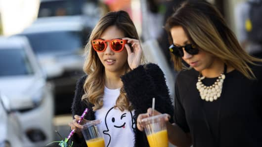 An employee wears a Snapchat ghost shirt and Snapchat Spectacles by Snap Inc. while crossing the street outside the company's office in the Venice neighborhood of Los Angeles, California.