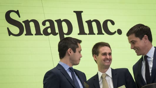 Snapchat co-founders Bobby Murphy (l) and Evan Spiegel (c) ring the opening bell on March 2, 2017, as NYSE President Thomas Farley looks on.