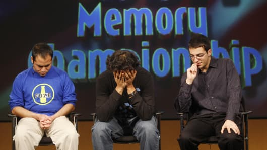 Ram Kolli (C) reacts after failing to remember the proper order of a deck of cards as Daniel Naftalovich (R) and eventual winner Chester Santos (L) compete in the final round of the 11th annual USA Memory Championship in New York March 8, 2008. The competition tests people's ability to rapidly memorize names, faces, words, playing cards and numbers while being timed as they try to recite them.