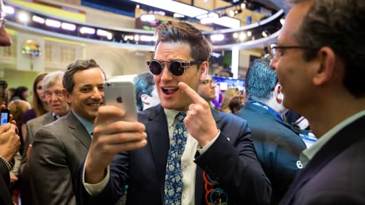 Matthew Kobach, manager of digital and social media at the New York Stock Exchange (NYSE), center, takes a selfie photograph wearing a pair of Snapchat Spectacles by Snap Inc. on the floor of the New York Stock Exchange (NYSE) during the company's initial public offering (IPO) in New York.