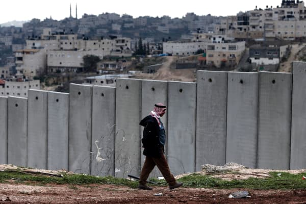 A Palestinian man walks past Israel's controversial separation barrier in the Palestinian neighborhood of Al-Tur.
