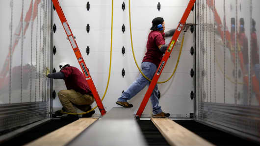 Workers install rivets inside a semitrailer on the factory floor at the Wabash National manufacturing facility in Lafayette, Ind.