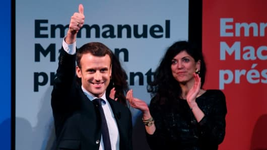 French presidential election candidate for the En Marche movement Emmanuel Macron (L) gestures during an event on International Women's Day on March 8, 2017.