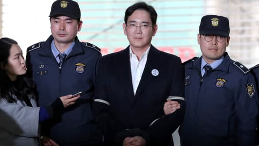 Jay Y. Lee, co-vice chairman of Samsung Electronics Co., center, is escorted by police officers as he arrives at the special prosecutors' office for questioning in Seoul, South Korea, on Saturday, Feb. 25, 2017.