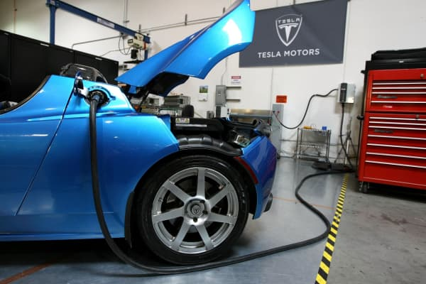 A power cable is seen plugged into a Tesla Roadster at the former Tesla headquarters in San Carlos.