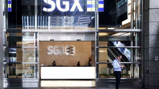 A man checks his phone at the entrance of the Singapore Exchange (SGX) headquarters in Singapore, on Thursday, Jan. 19, 2017.